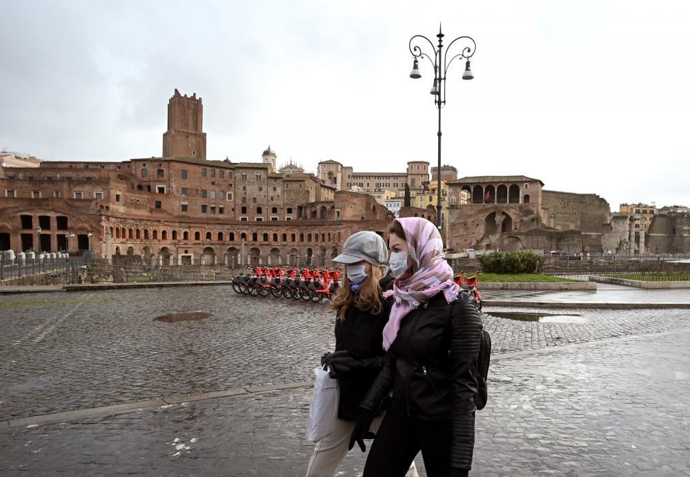 Mulheres usam máscaras protetoras contra o Covid-19 em frente ao Fórum de Trajano, em Roma, na Itália, na terça-feira (3) — Foto: Vincenzo Pinto / AFP
