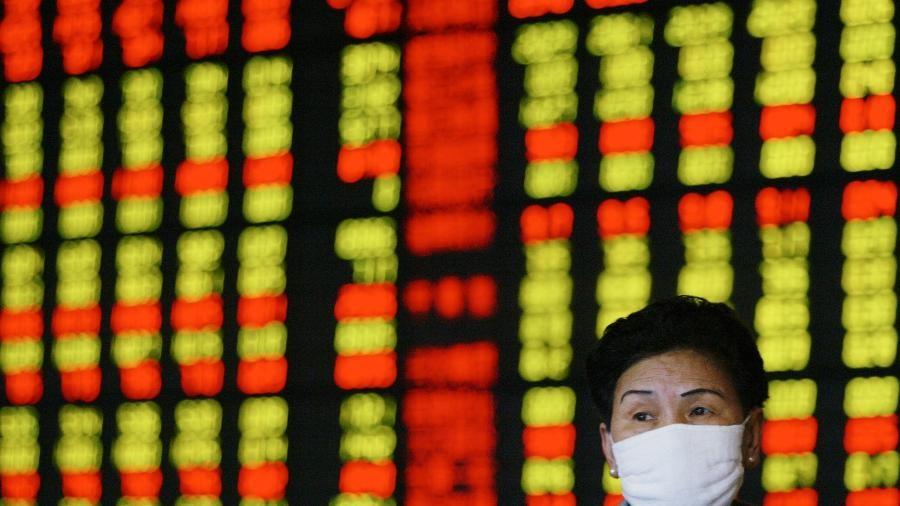 Investidora usa máscara de prevenção contra vírus enquanto monitora ações em Xangai, ChinaImagem: Claro Cortes