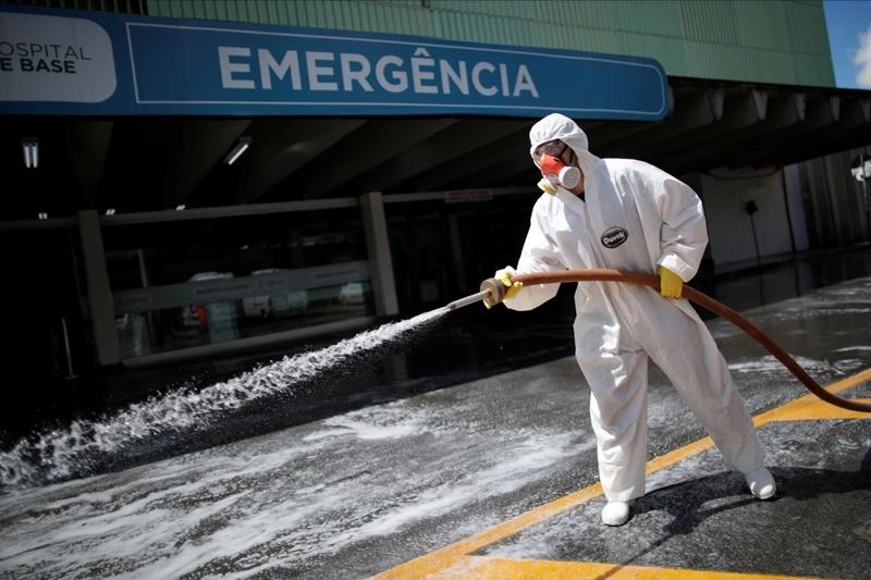 Integrante das Forças Armadas desinfeta a entrada do Hospital de Base do Distrito Federal contra o coronavírus, em Brasília, nesta terça-feira.UESLEI MARCELINO / REUTERS